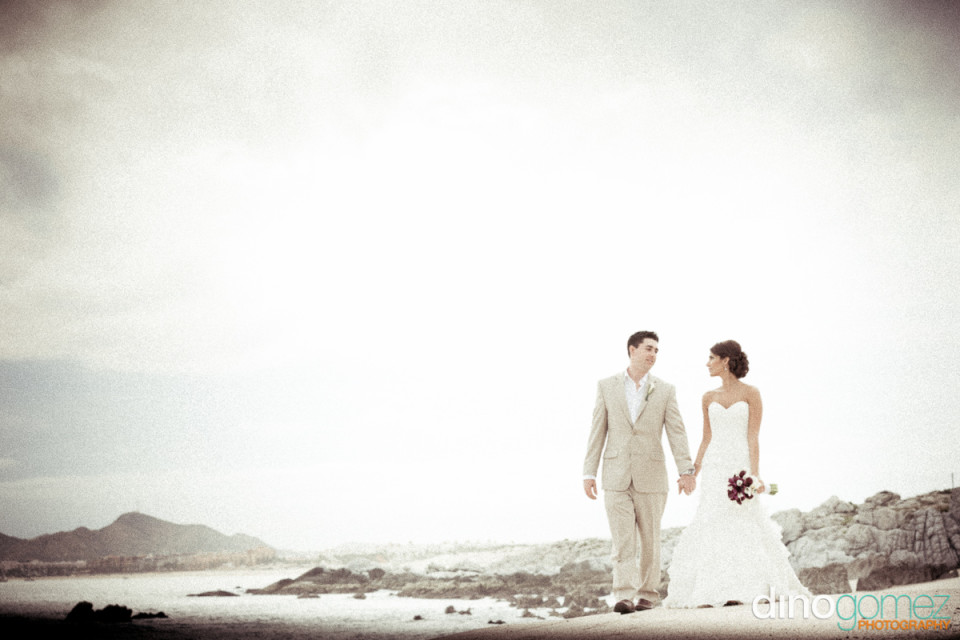 Bride and groom holding hands on the beach while looking at each other in Los Cabo Mexico