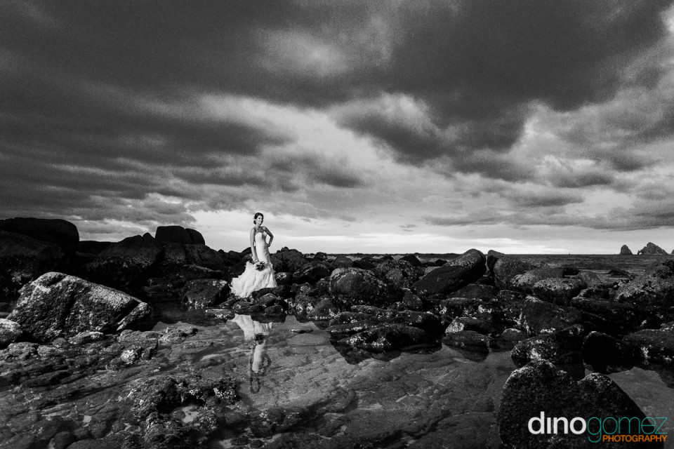 Black and white shot of the bride posing on the rocks by destination wedding photographer Dino Gomez