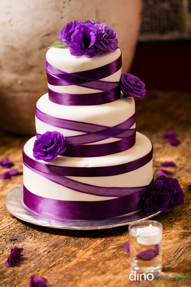 Three tier wedding cake with purple ribbons and flowers