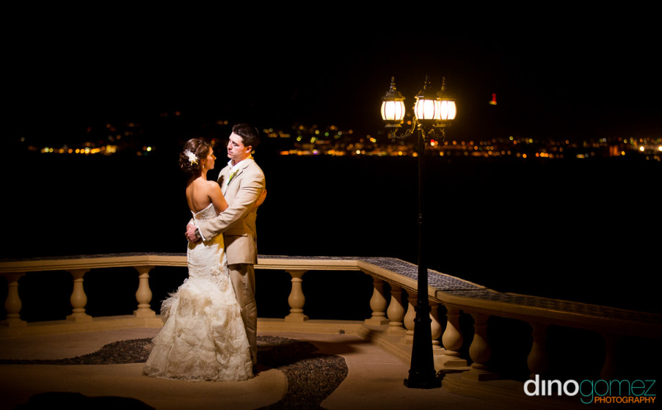 Bride and groom out on the balcony at night in Mexico