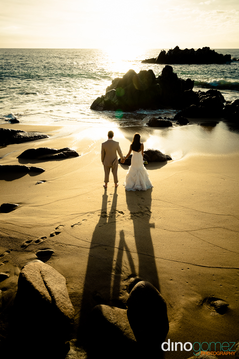 Newlyweds holding hands on the beach and looking at the sunset across the ocean