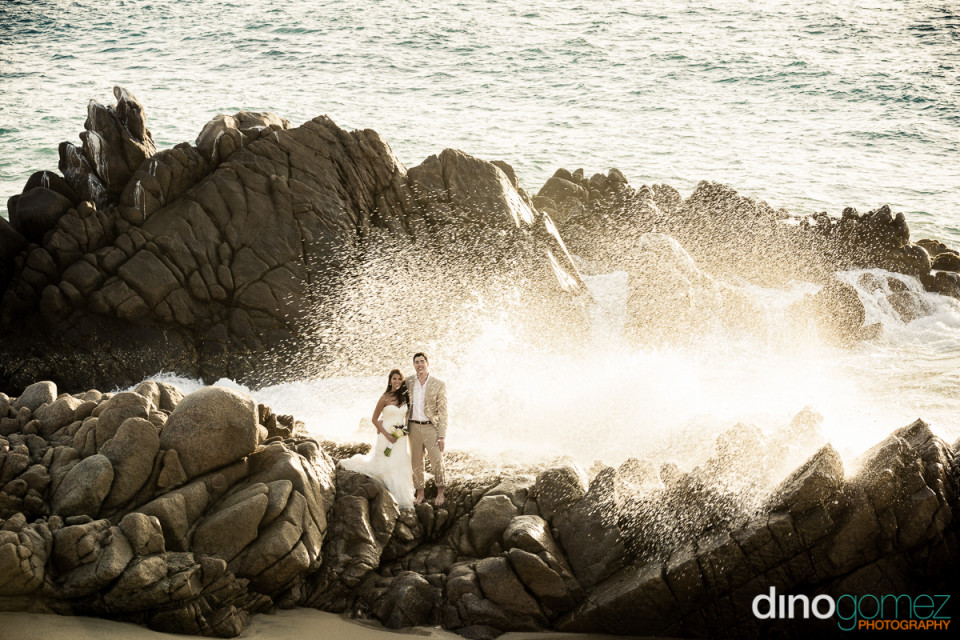 Beautiful shot of the happy bride and groom standing on rocky beach by wedding photographer Dino Gomez