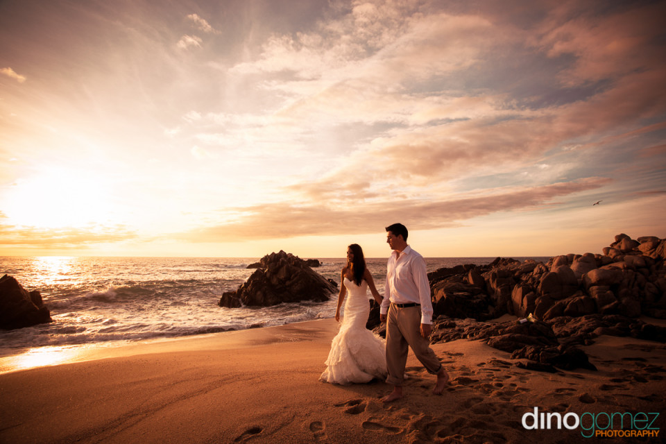 Bride and groom enjoying an amazing sunset on a beach in Los Cabos Mexico