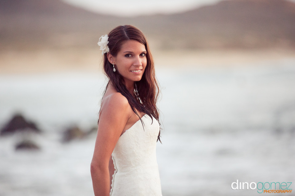 Side view of a bride with a flower in her hair by wedding photographer Dino Gomez