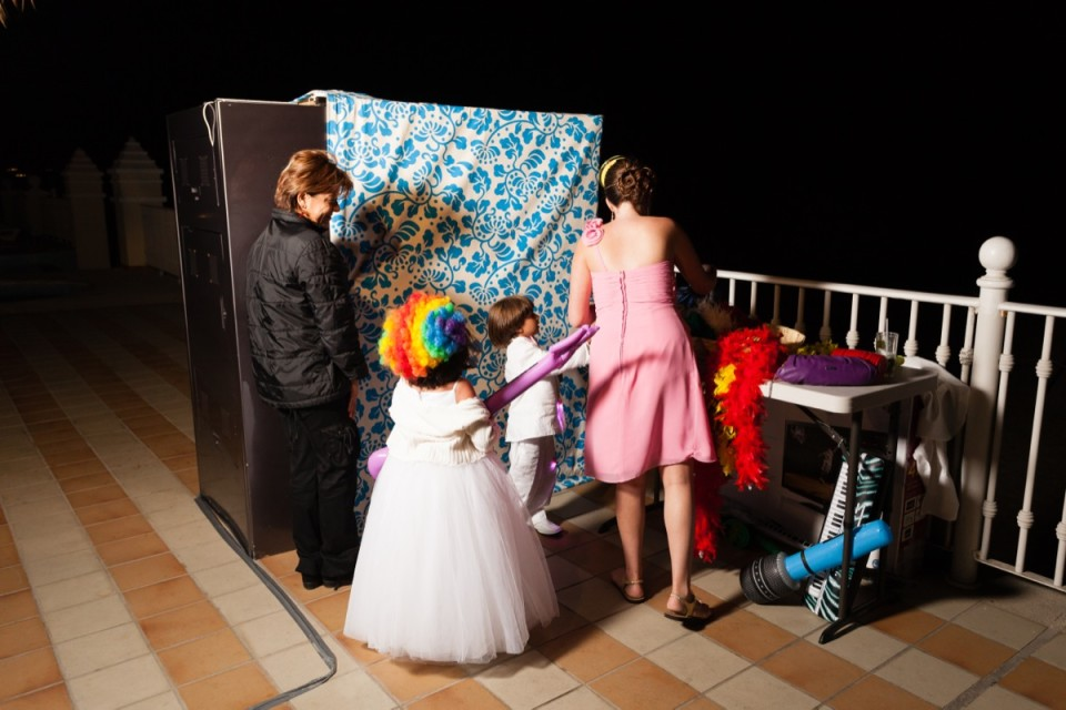 Some wedding guests decide which props they will use while they wait their turn for the photo booth