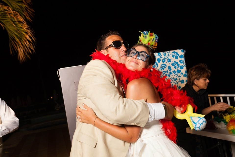 A bride and groom dress uo in a feather boa and sunglasses and enjoy the evening together