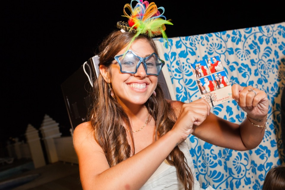 Party guest wearing sunglasses shows photographer Dino Gomez her photo booth shots