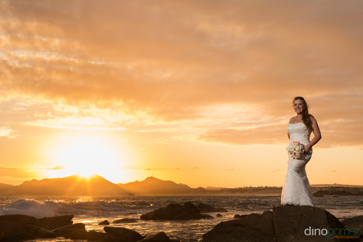 Bride with her wedding bouquet on the beach at sunset