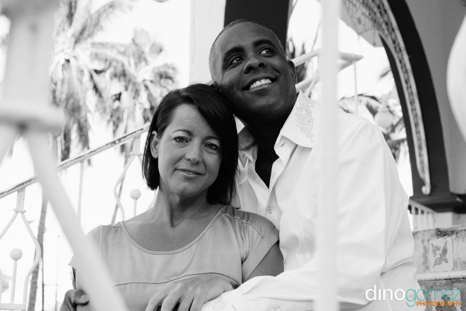 Black and white shot of an interracial couple sitting on the stairs and smiling