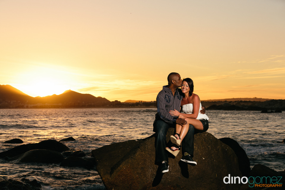 Beautiful couple sitting on a rock in Mexico with the beach and the beautiful sunset as the backdrop