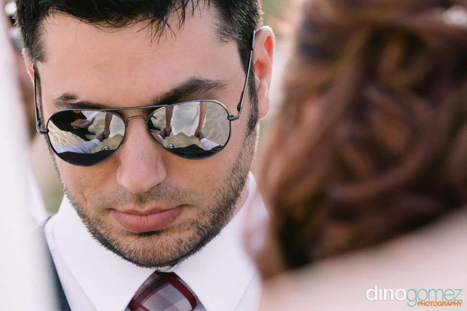 Closeup of groom with the reflection of hhim holding the bride's hand in his sunglasses