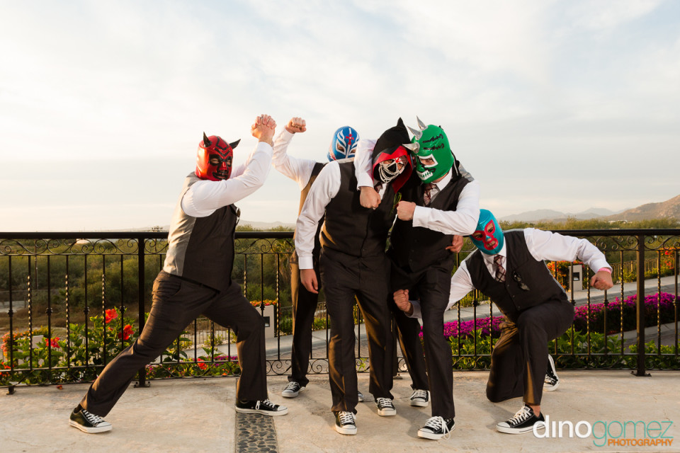 Groom and groomsmen wearing super hero masks and having fun