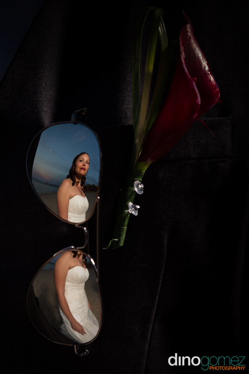Bride's reflection in aviator glasses on a jacket