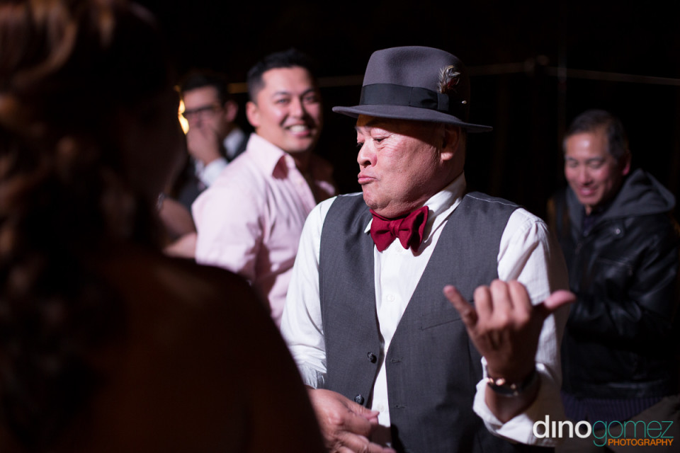 Man in a fedora shares a moment of air guitar fun at wedding reception