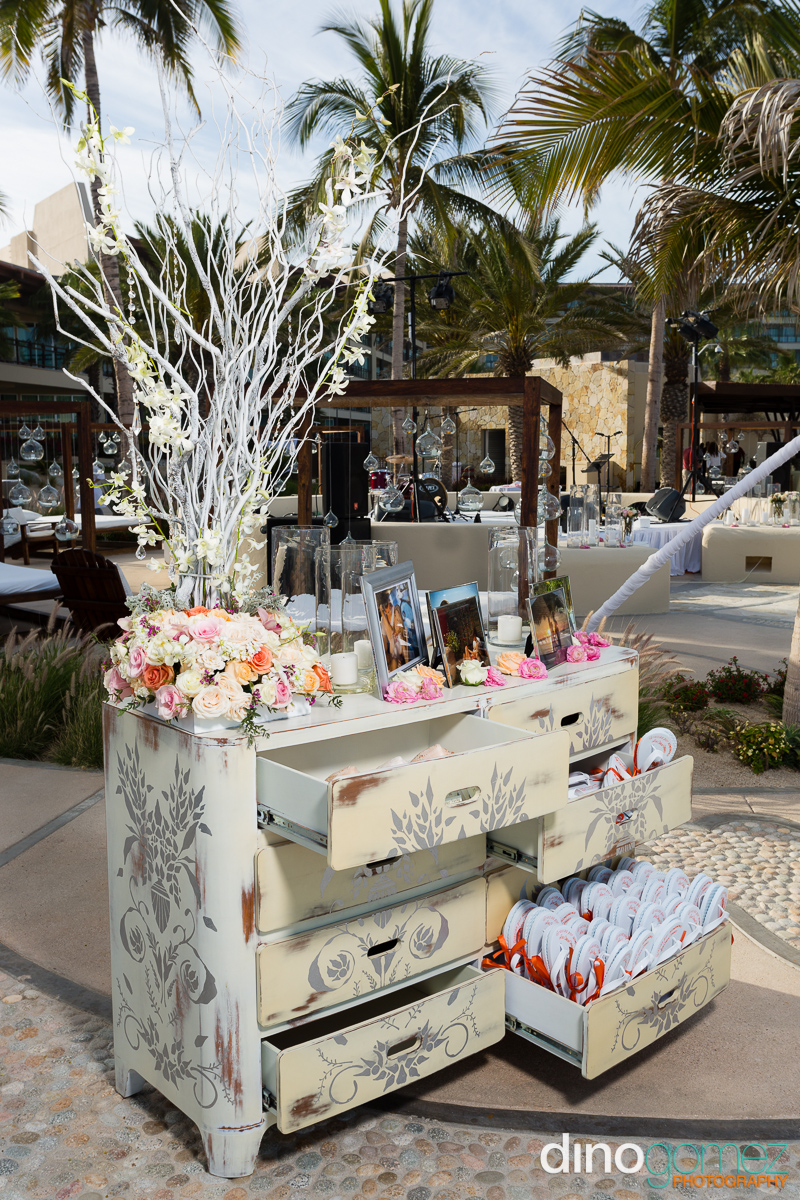 Chest of drawers re-purposed as wedding flip flop station and decorated with pictures of the bride and groom