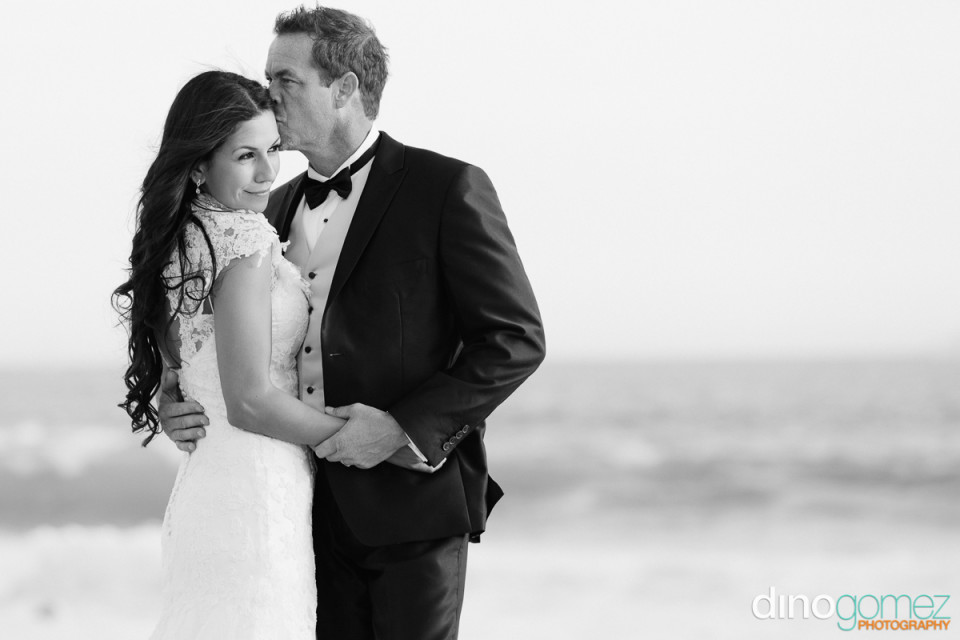 Loving groom kissing his bride's forehead in black and white by destination wedding photographer Dino Gomez