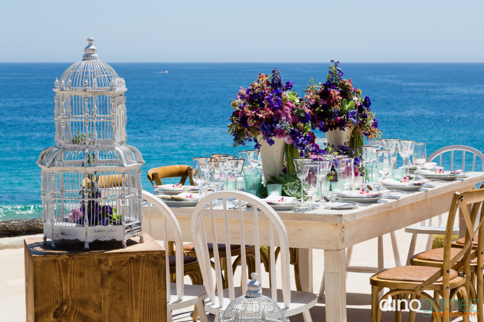 Destination wedding reception table with a bird cage and ocean views