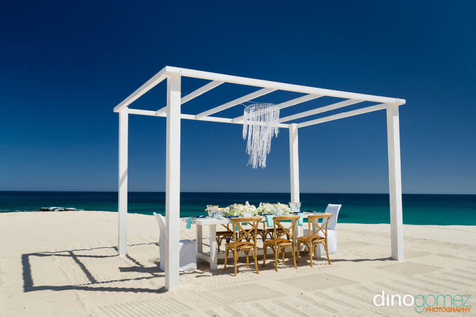 Beautiful outdoor wedding reception table on the sand under a white trellis