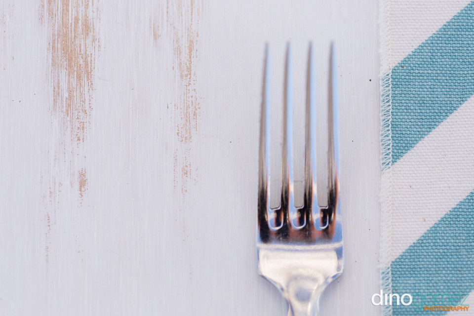 Silver fork on white painted table next to a striped table cloth
