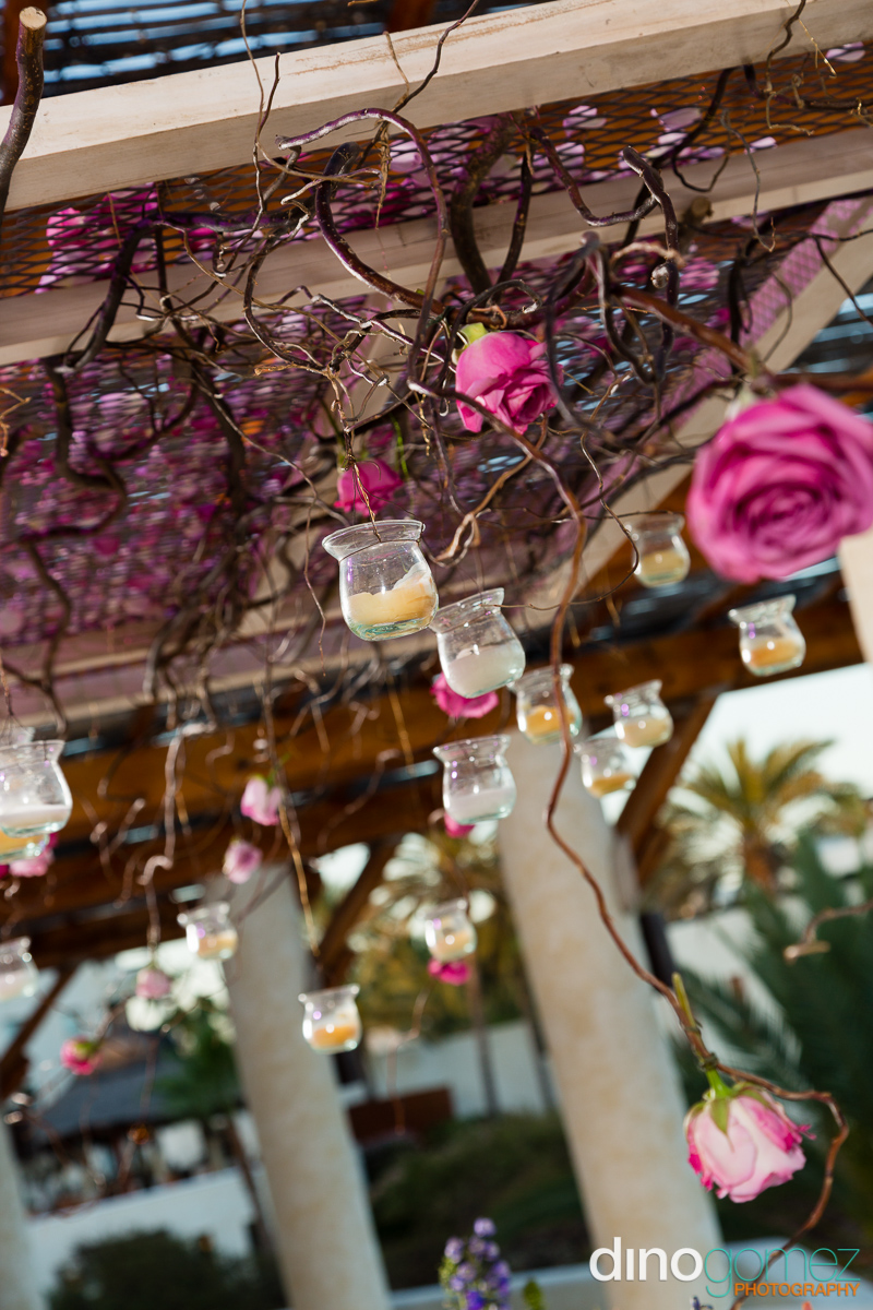 Wedding candles in glass jars hanging from trellis with pink roses