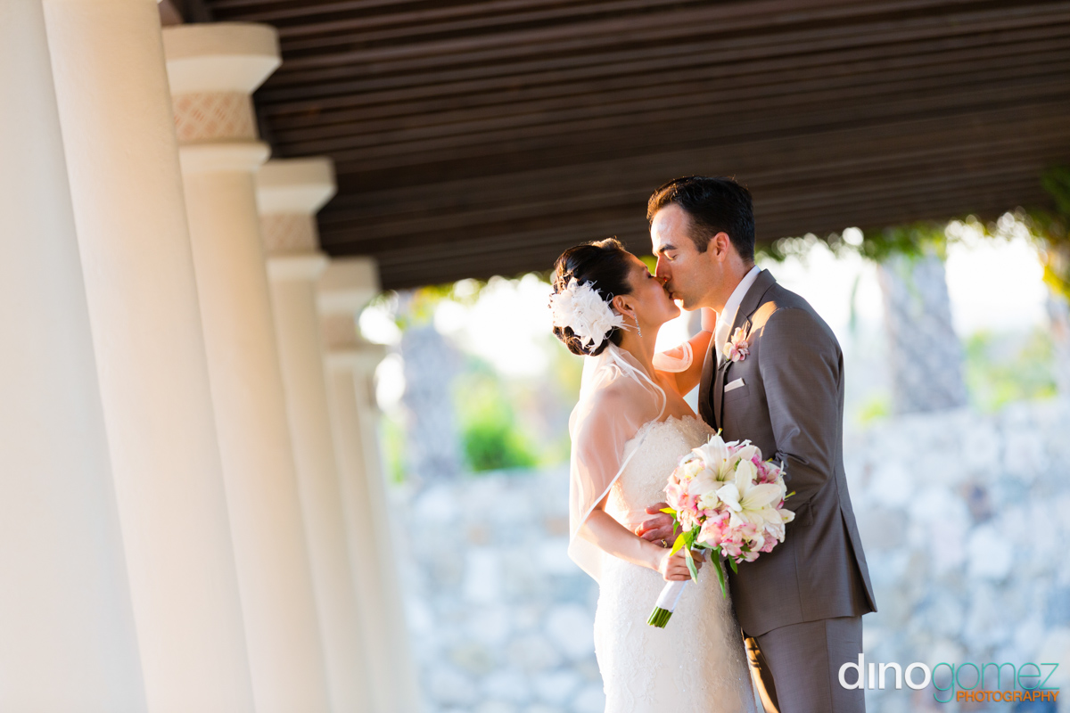 Gorgeous couple sharing a kiss as husband and wife at their destination wedding