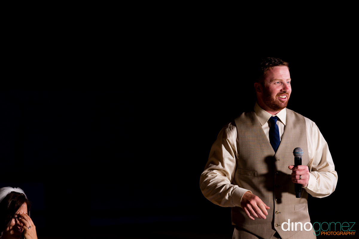 Groom holding a mike and his bride crying in the corner at the destination wedding in Mexico