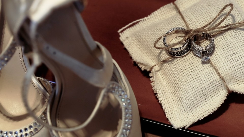A close up of two wedding rings resting on a linen pillow tied with string. Photograph taken by Dino Gomez.