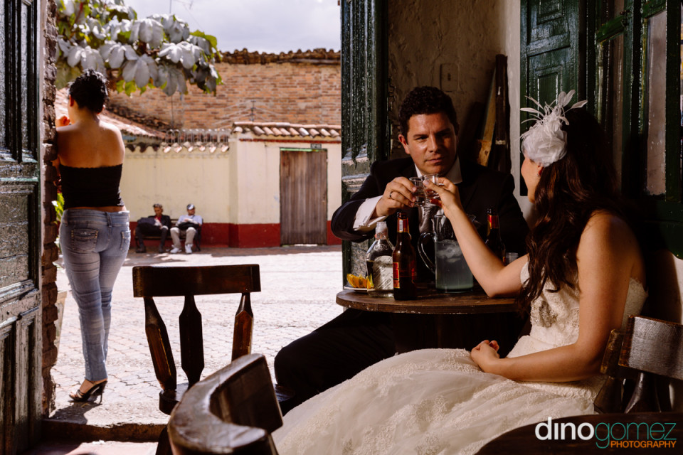 Lovely wedding day photo of bride and groom having shots around a small table in Mexico