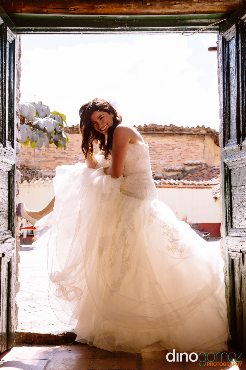 Bride posing in a doorway and showing off her wedding dress and shoes