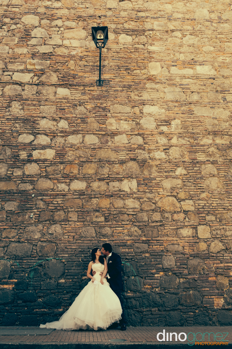 Bride and groom embracing on a cobbled street in Mexico