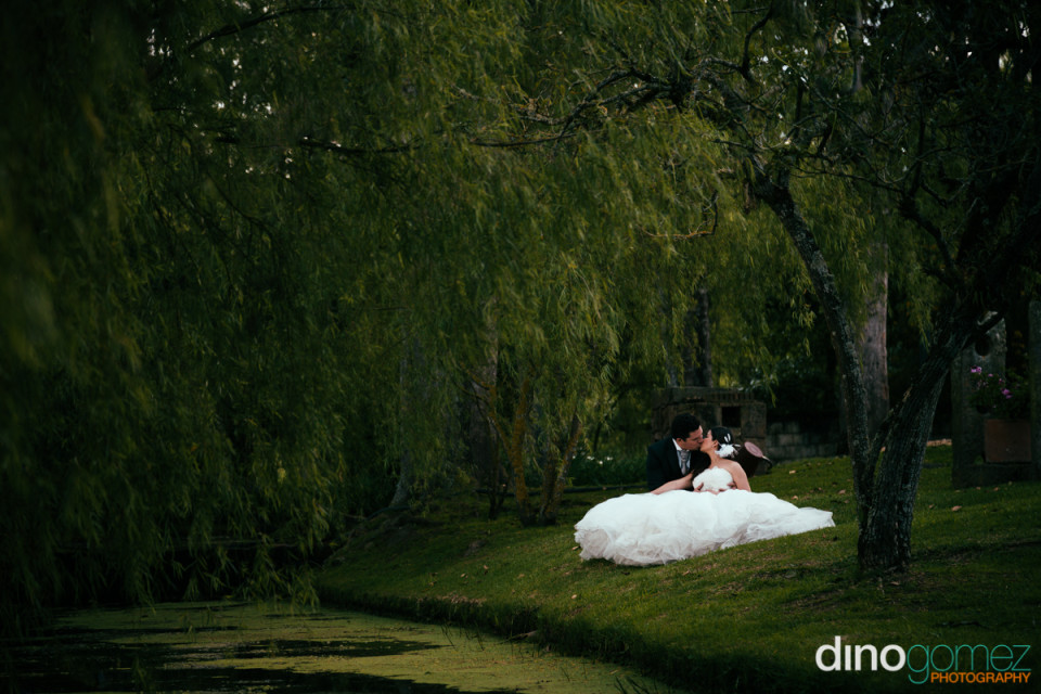 Newlyweds kissing in a lush setting with the river below on their wedding day