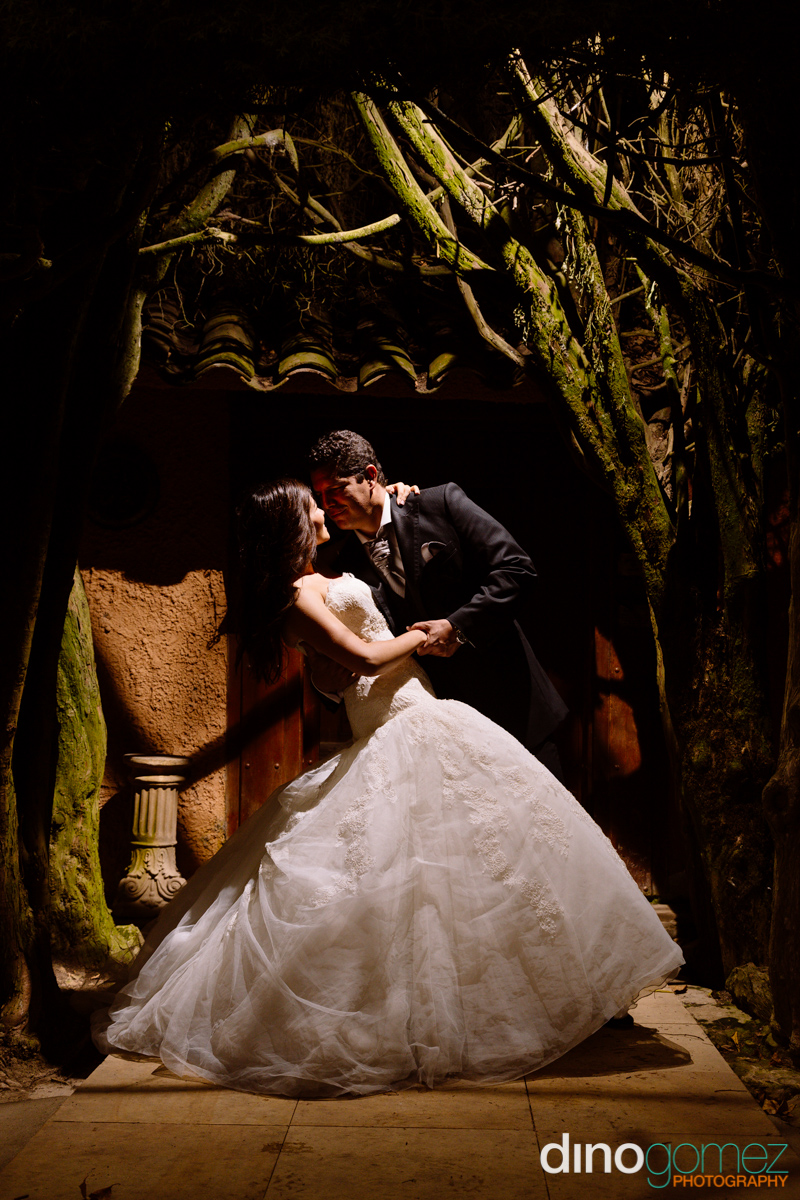 Bride and groom dancing in the night under a tree in Mexico