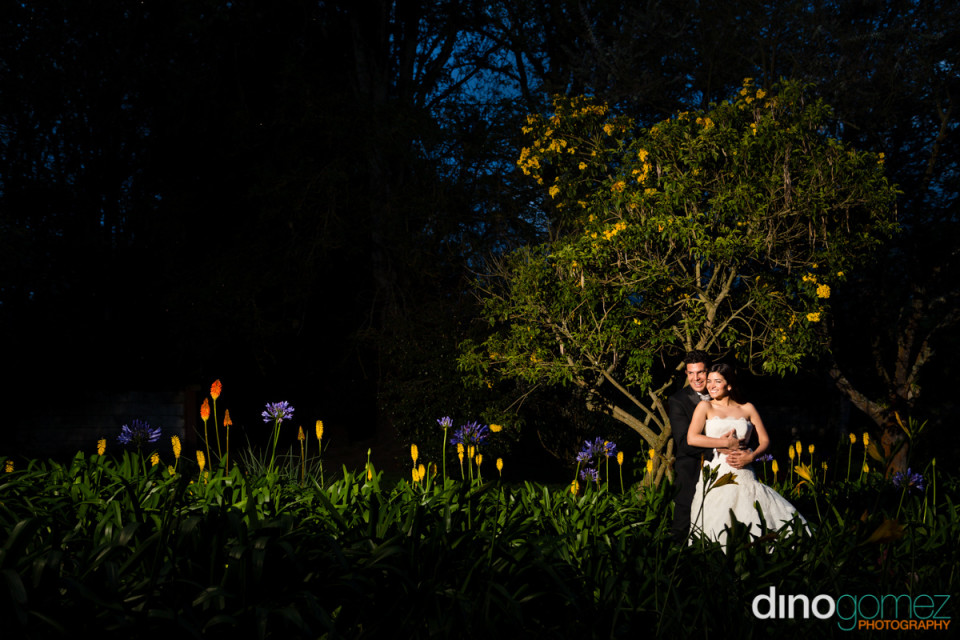 Destination wedding bride and groom embrace from behind while surrounded by lush flowers and trees