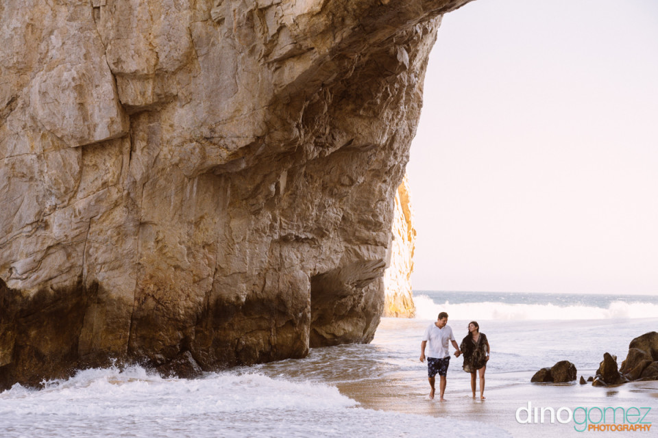Couple holding hands and walking on the beach by destination wedding photographer in Cabo Dino Gomez