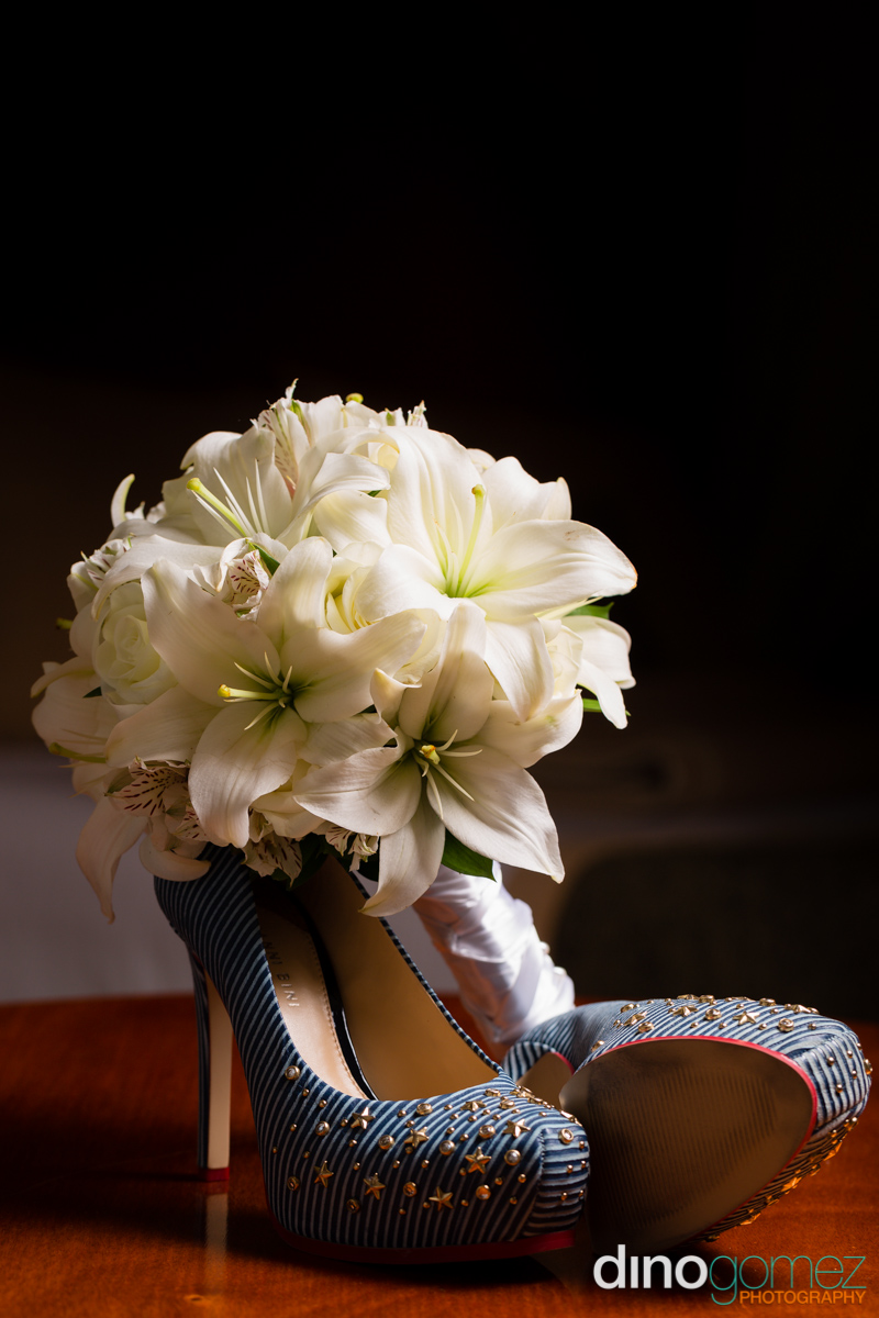 A shot of a bouquet of white wedding flowers behind a pair of blue studded shoes by photographer in Cancun Dino Gomez