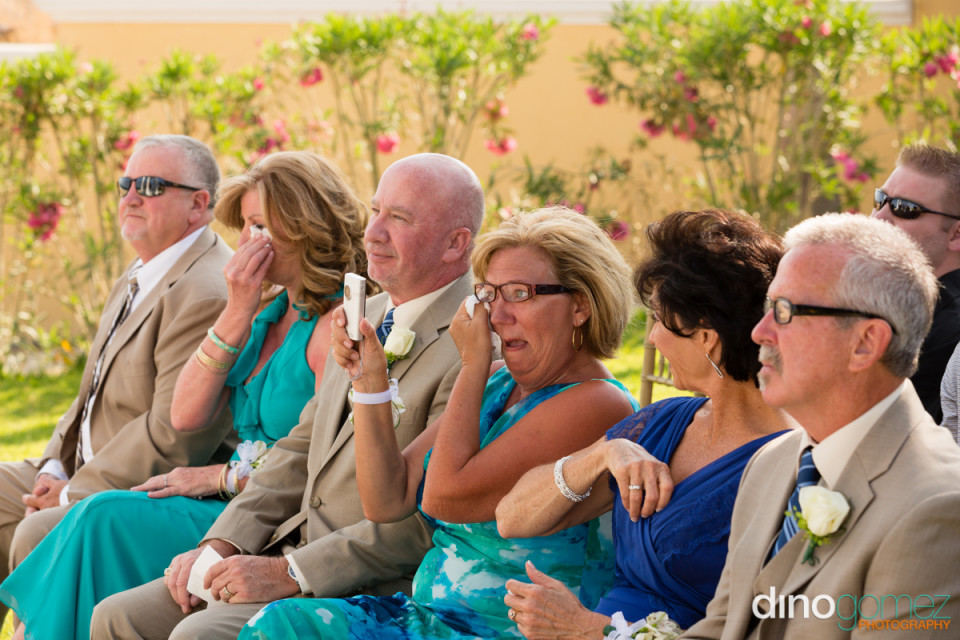 Ladies in blue crying during the wedding ceremony by photographer in Cancun Dino Gomez