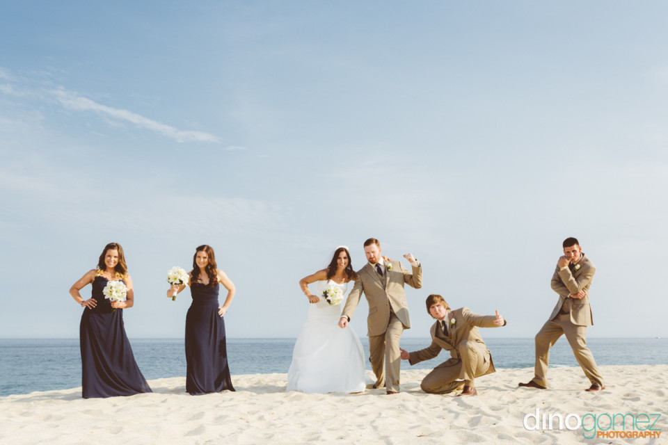 Bridal party posing on the beach with the new husband and wife in Mexico