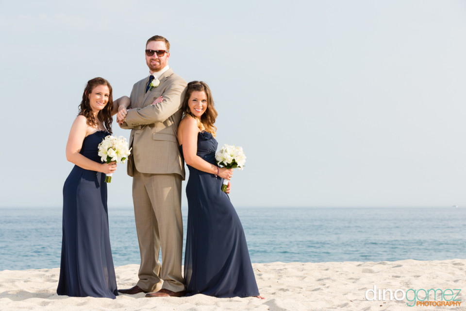 Groom posing with the bridesmaids on the beach by the talented destination wedding photographer Dino Gomez