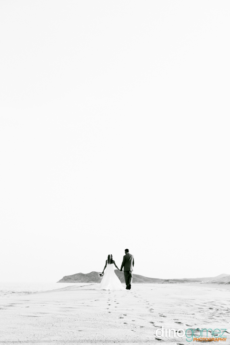 Newlyweds walking on the sand and holding hand in Los Cabos Mexico