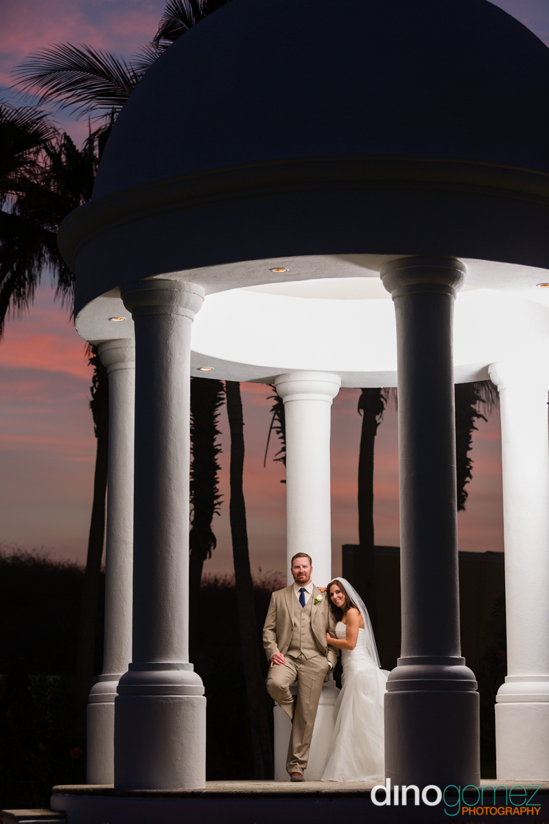 Newlyweds posing under a Gazebo with the bride leaning on her groom