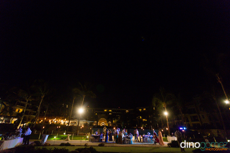 This destination wedding photgraph shows the atmospheric image of a wedding party by moonlight overlooked by majestic palm trees.