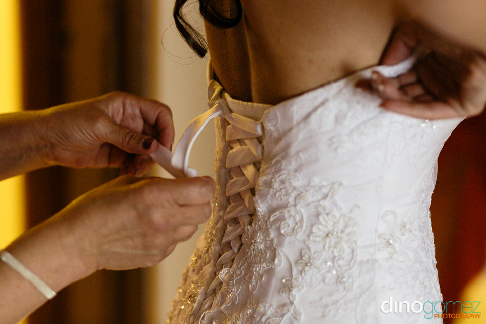 The bride getting ready with a pair of hands helping with her wedding dress