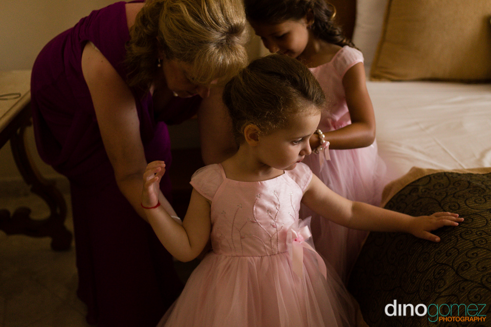 Beautiful shot of the flower girl in a pink dress getting ready by wedding photographer in Cabo Dino Gomez