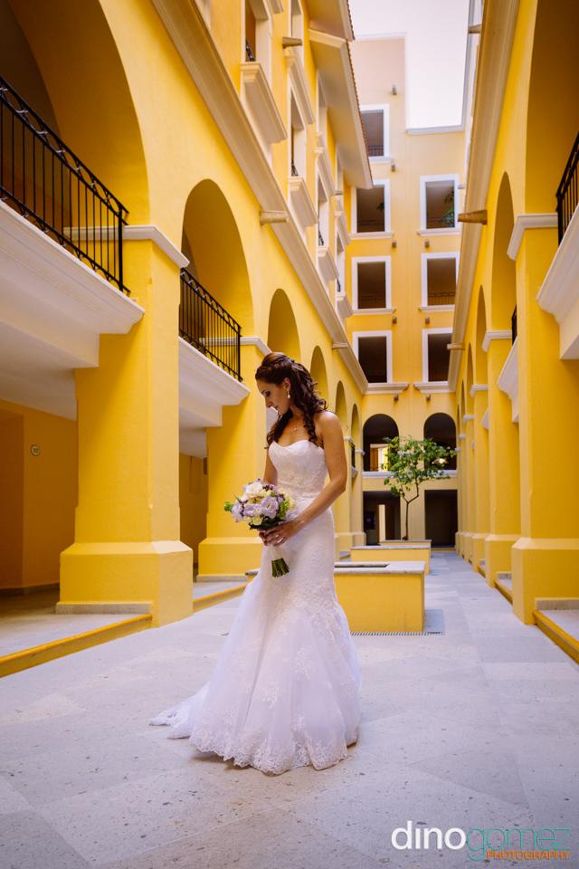 Gorgeous bridal portrait with the bride holding a bouquet of flowers in a yellow building