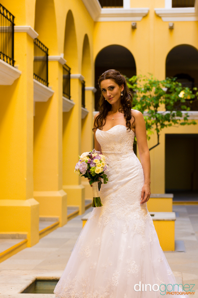 Bride smiling and holding a bouquet of flowers at her destination wedding in Cabo Mexico