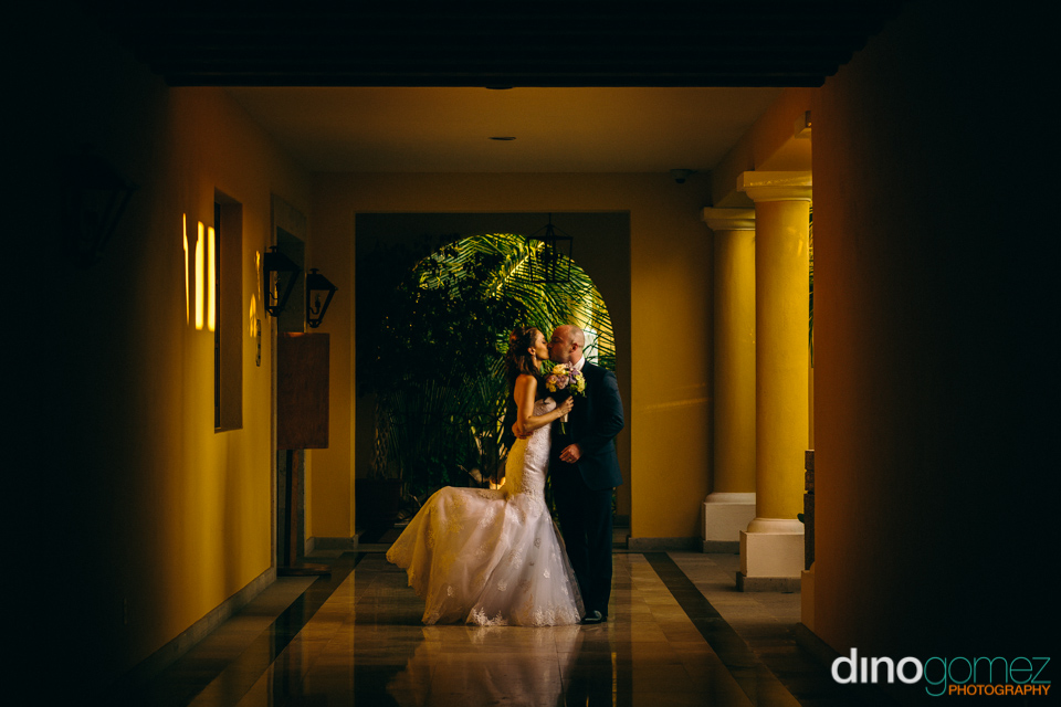Newlyweds kissing inside a sunset coloured building in Mexico