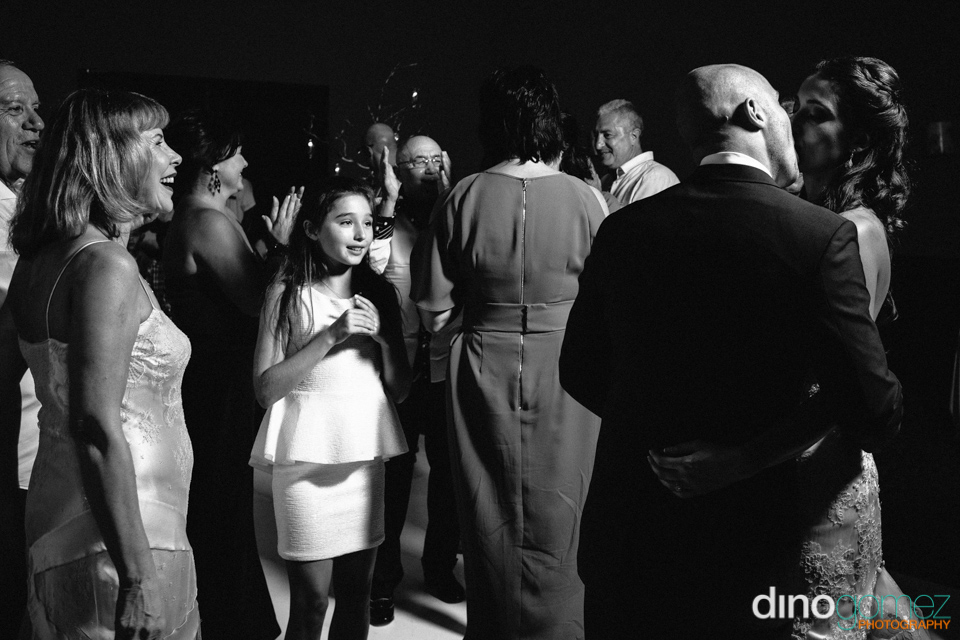 Black and white shot of the newlyweds wedding kissing with the crowd looking on