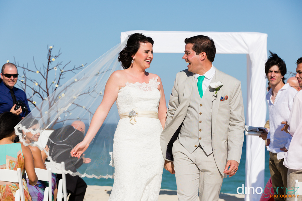The Bride And Groom Laughing And Walking Down The Beach At Their Destination Wedding In Mexico