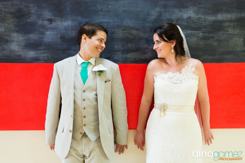Newly weds leaning on a black and red wall in Mexico