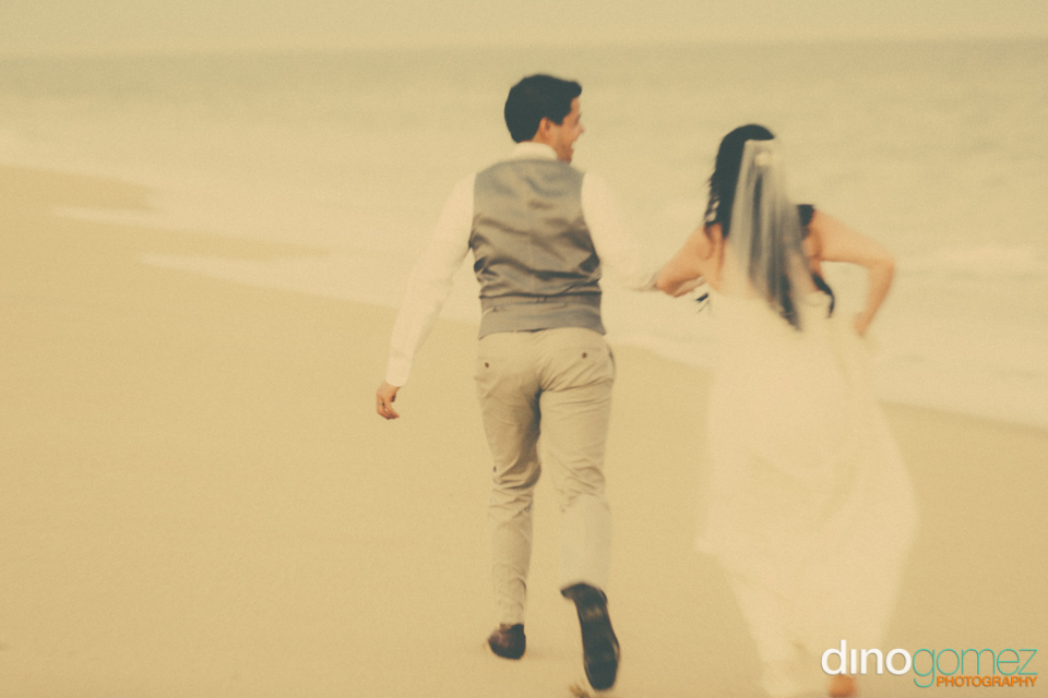 Colour shot and back view of the bride and groom running on the beach in Cabo Mexico